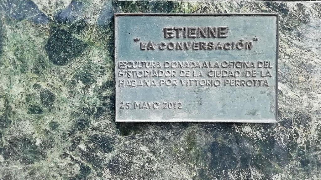 Placa de bronce colocada sobre el Zócalo de la estatua La Conversación en la Plaza de San Francisco de Asís en La Habana