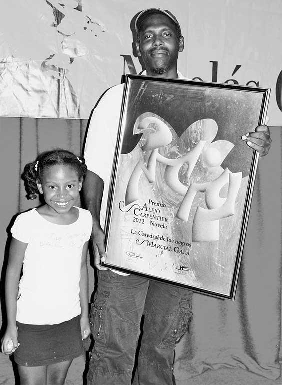 Marcial Gala con una de sus hijas recogiendo el Premio Alejo Carpentier 2012